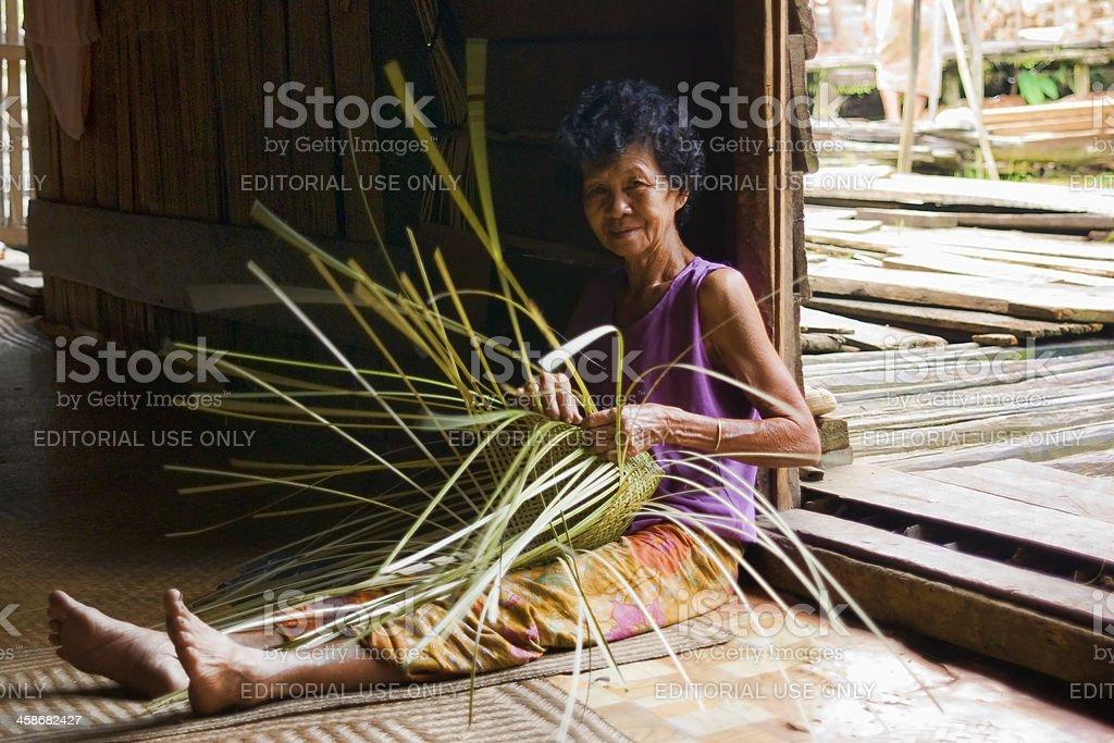 Old woman braiding a basket stock photo