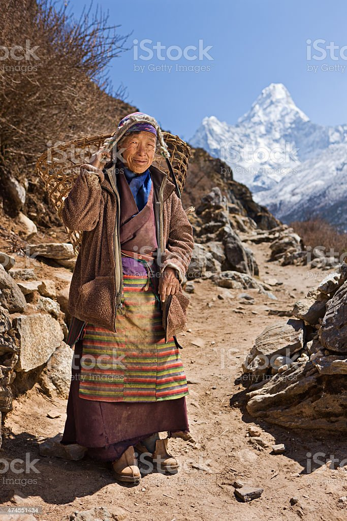 Old woman carrying basket in Himalayas stock photo
