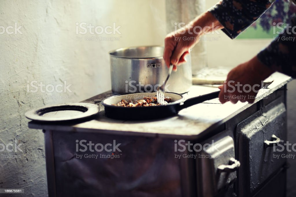 Old woman cooking meat stock photo
