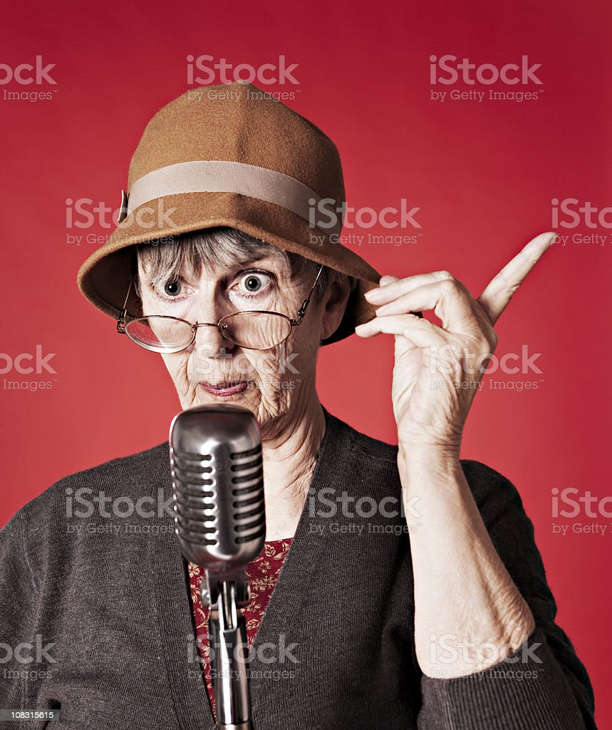Old woman delivers lecture into microphone royalty-free stock photo