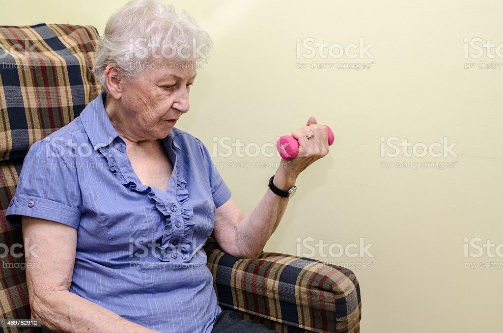 Old woman doing wrist exercise stock photo