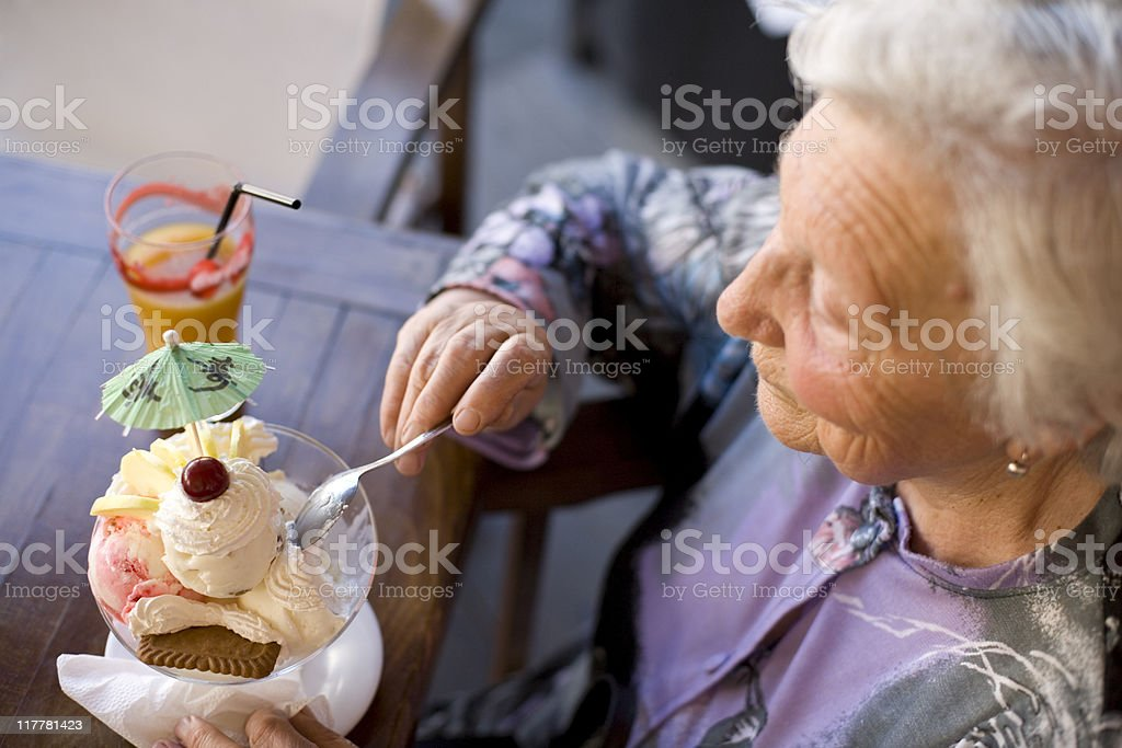 Old woman eating icecream royalty-free stock photo