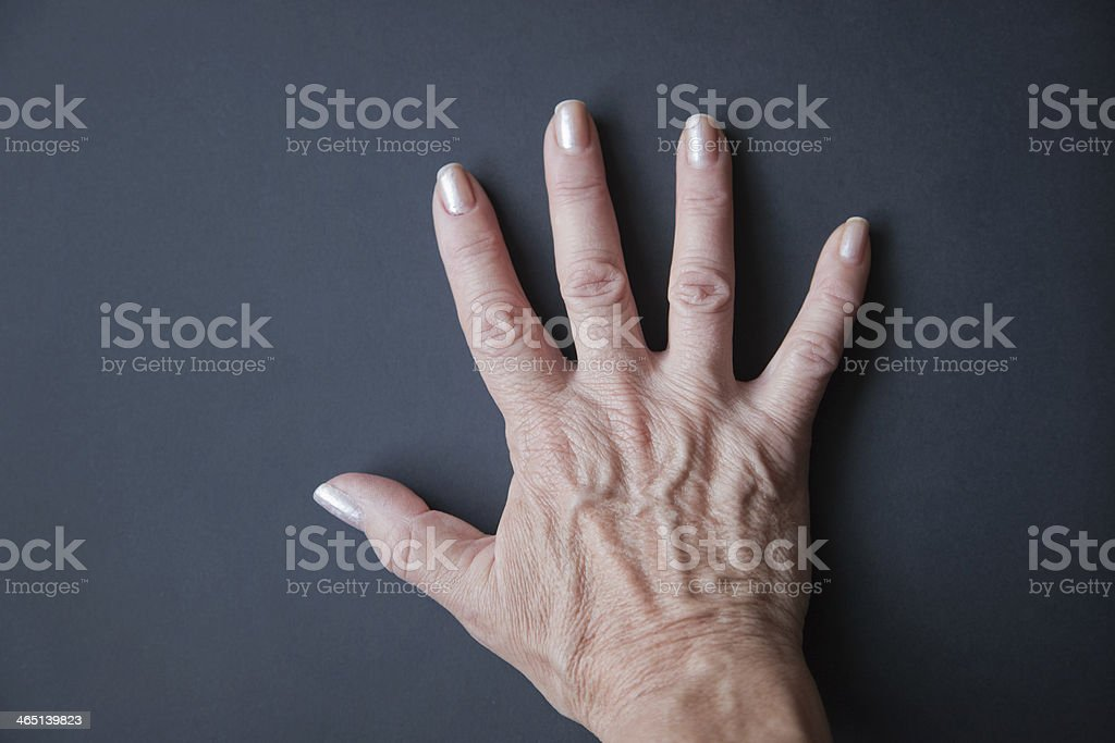 Old woman hand on a grey background. stock photo