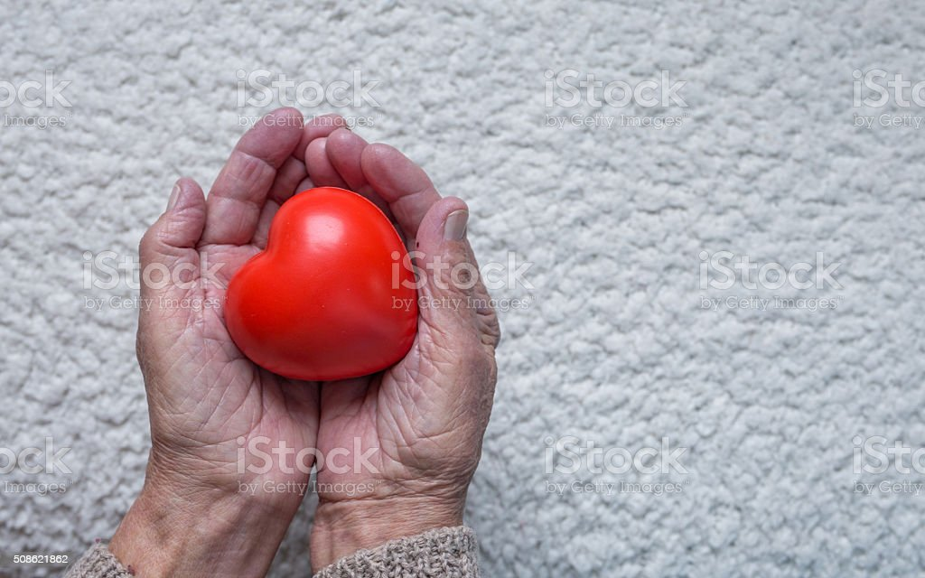 Old woman hands holding red heart, top view stock photo