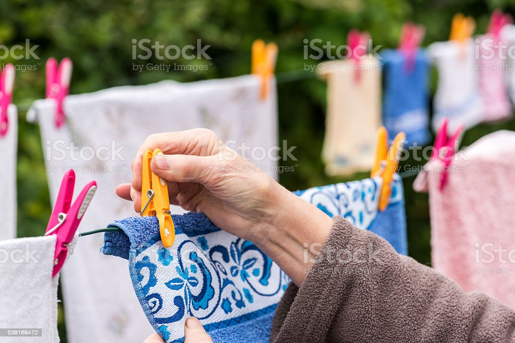 Old woman hanging laundry outdoor stock photo