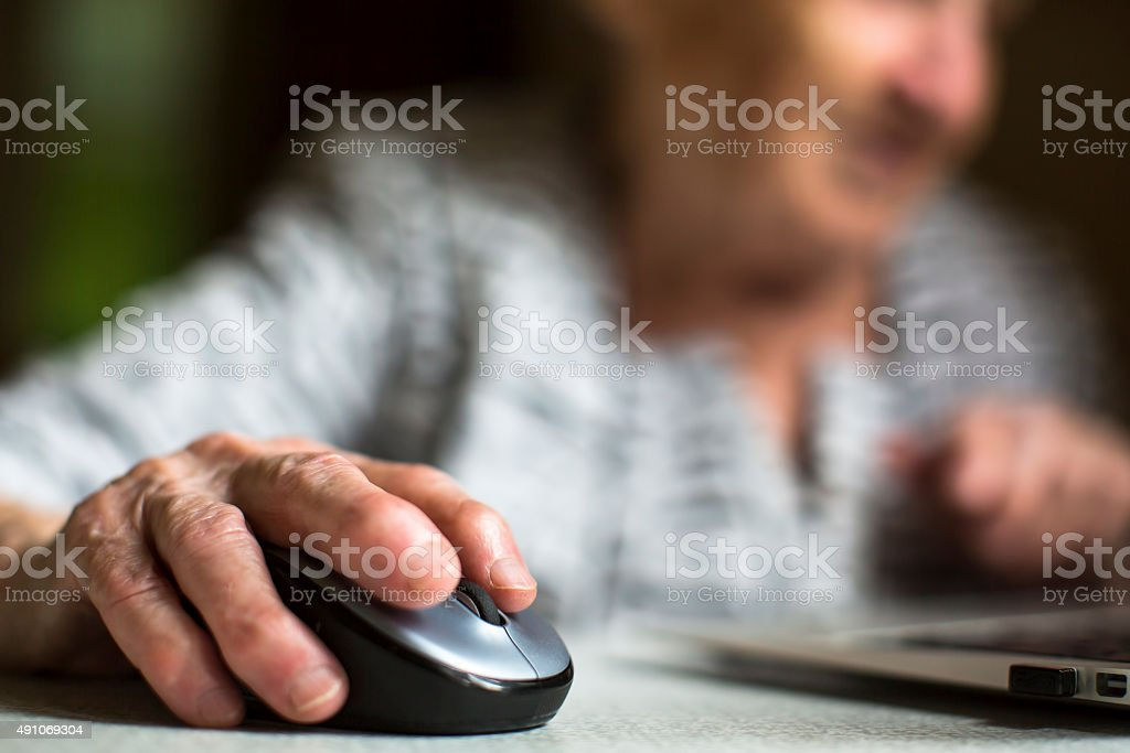 Old woman holding a computer mouse. stock photo