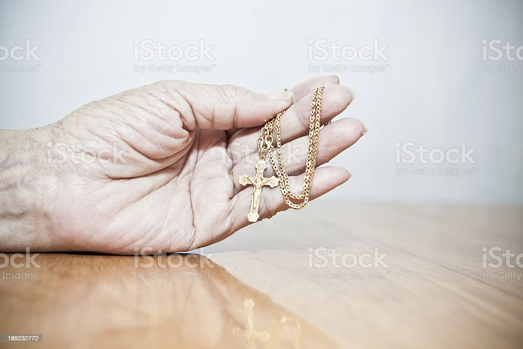 Old woman holding gold crucifix in hand royalty-free stock photo