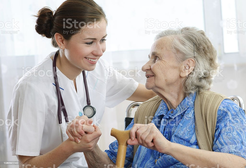 Old woman holding hands with female caregiver stock photo
