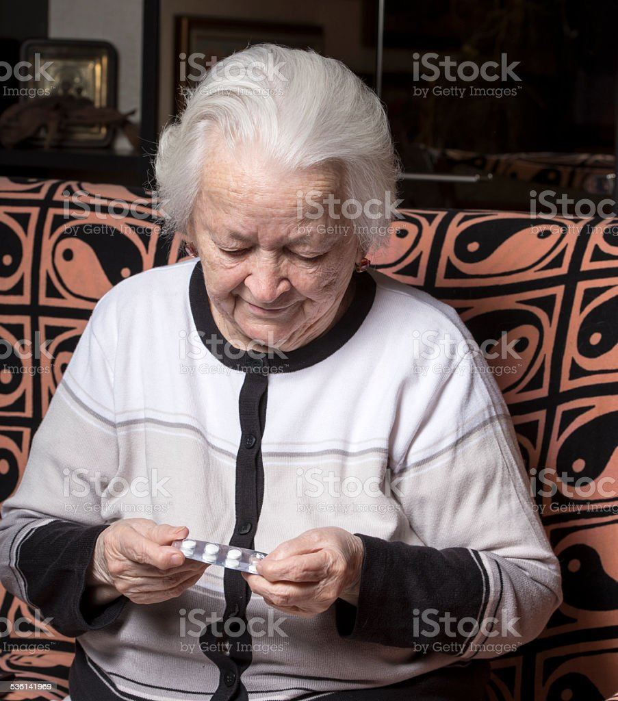 Old woman holding pills stock photo