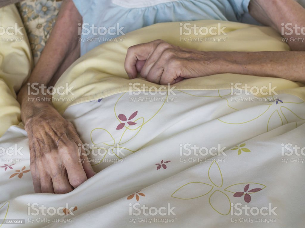 Old woman in a bed stock photo