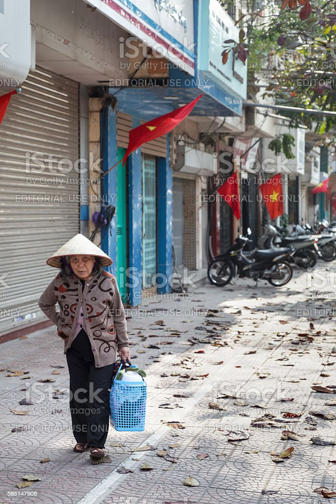 Old woman in a typical Hanoi street stock photo