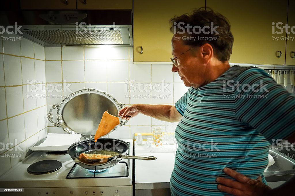 Old woman in kitchen, baking fresh dough in oil. stock photo