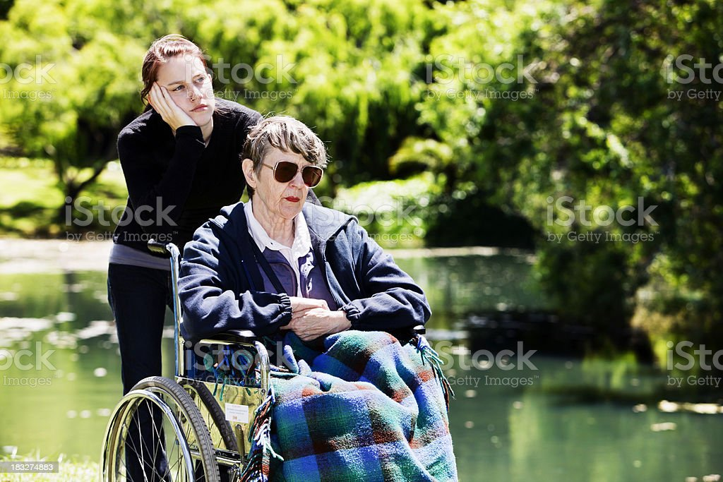 Old woman in wheelchair and teenager, both bored, depressed royalty-free stock photo