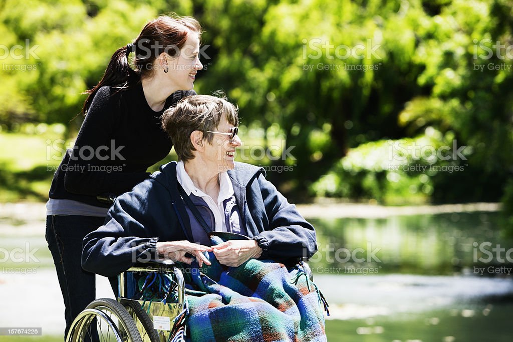 Old woman in wheelchair and teenager enjoy outing to park royalty-free stock photo