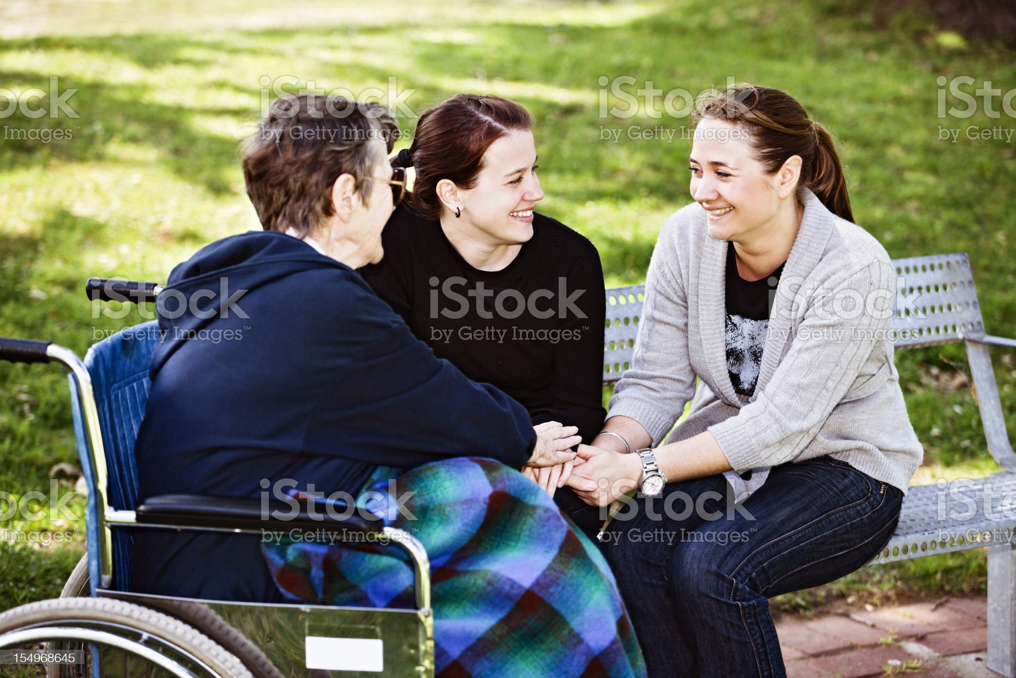 Old woman in wheelchair and two young women clasp hands royalty-free stock photo
