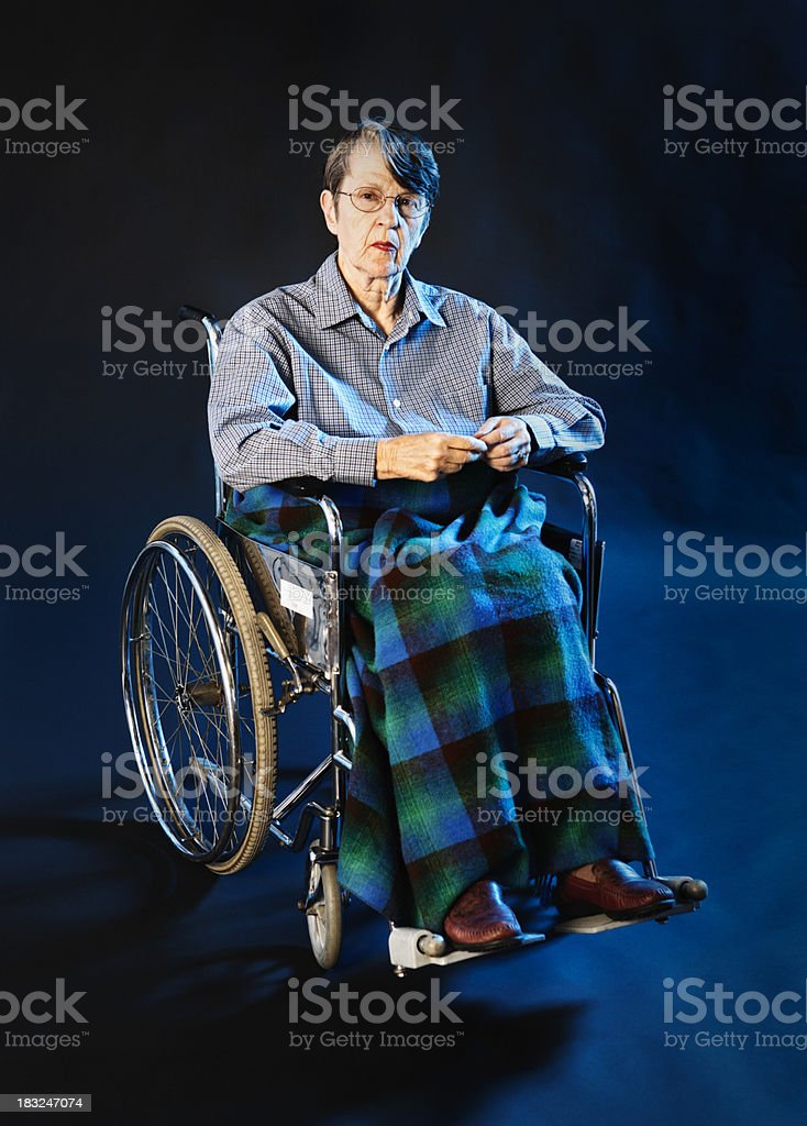 Old woman in wheelchair looks at camera, undefeated royalty-free stock photo