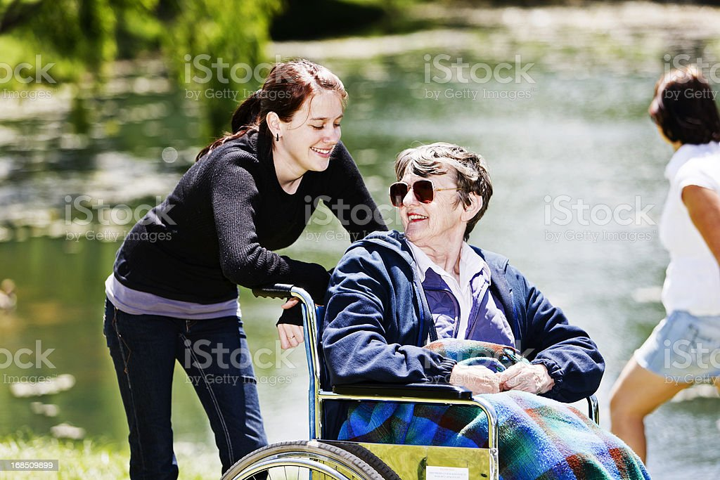 Old woman in wheelchair looks round affectionately at smiling caregiver royalty-free stock photo