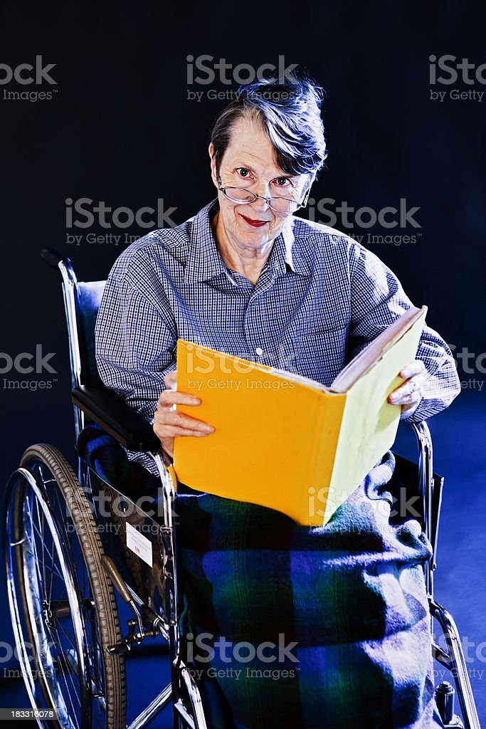 Old woman in wheelchair looks up smiling from yellow book royalty-free stock photo