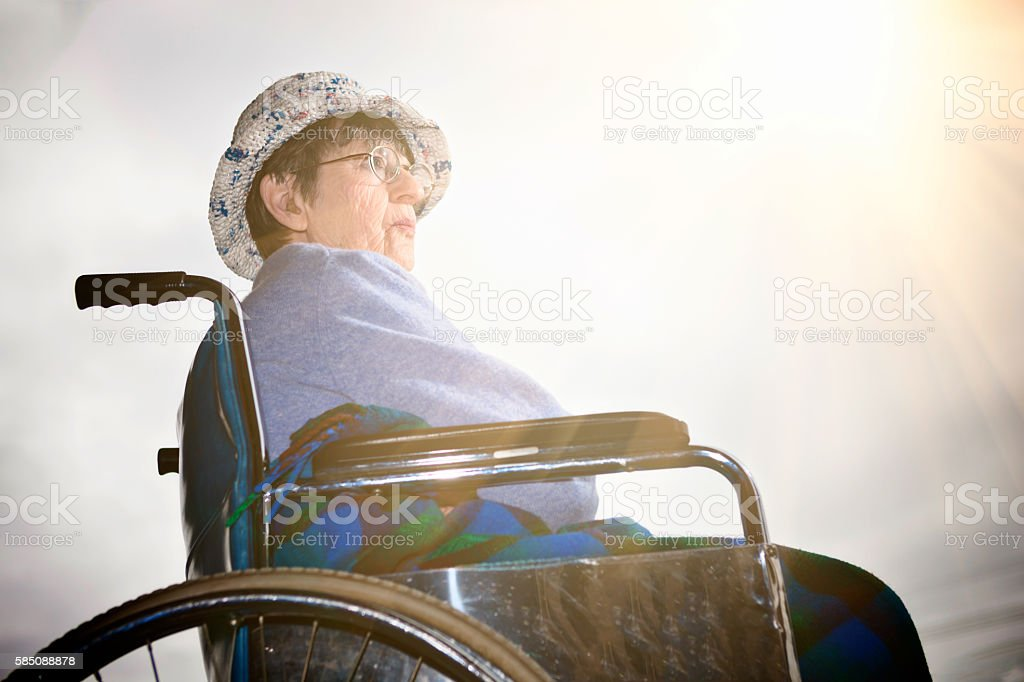 Old woman in wheelchair sits in the sun, looking hopeful stock photo