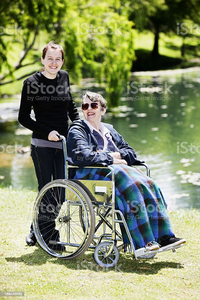 Old woman in wheelchair smiles at her equally happy caregiver royalty-free stock photo