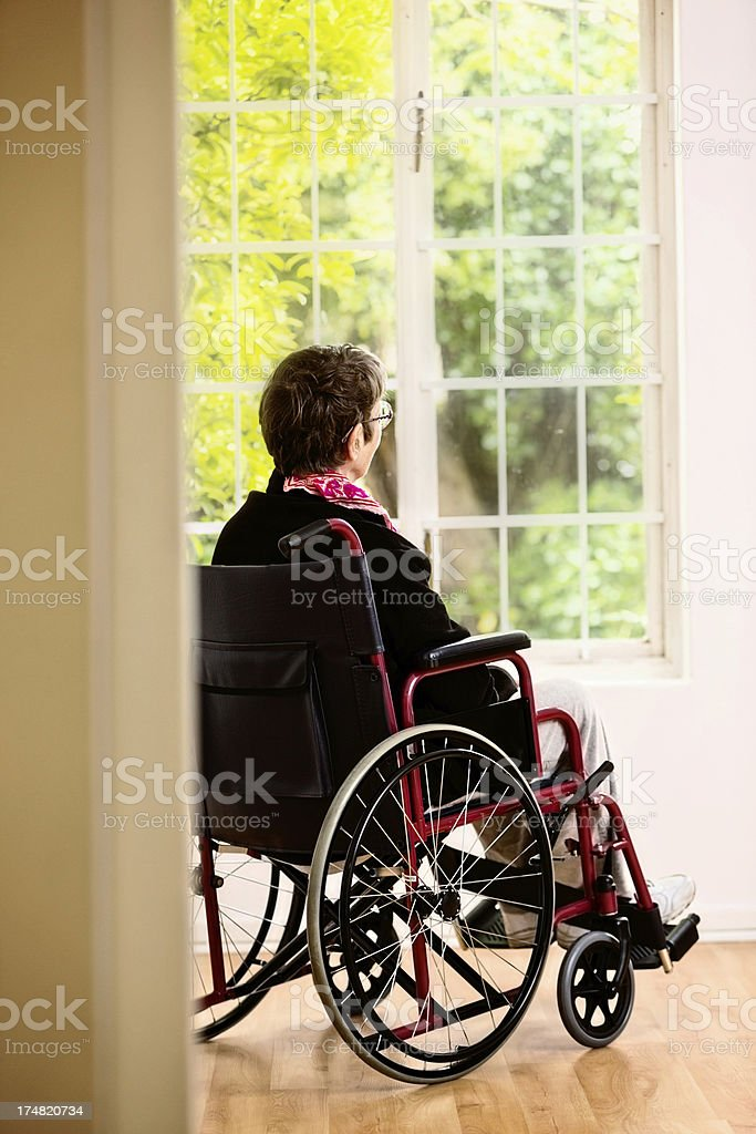 Old woman in wheelchair wistfully watches garden she cannot reach royalty-free stock photo