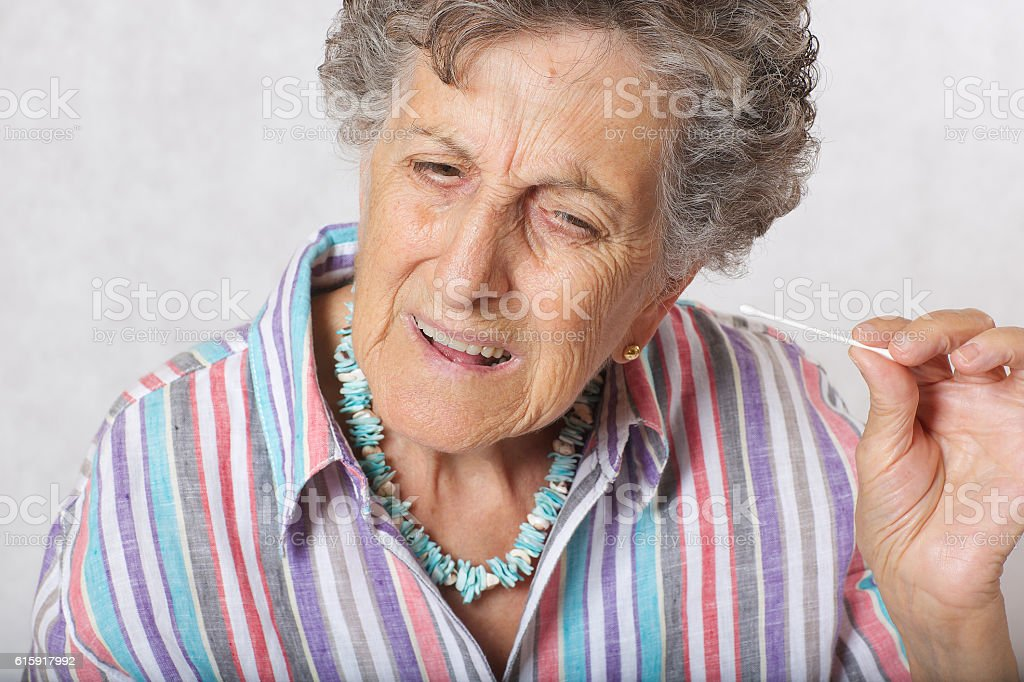 Old woman is cleaning her ears with cotton swab stock photo
