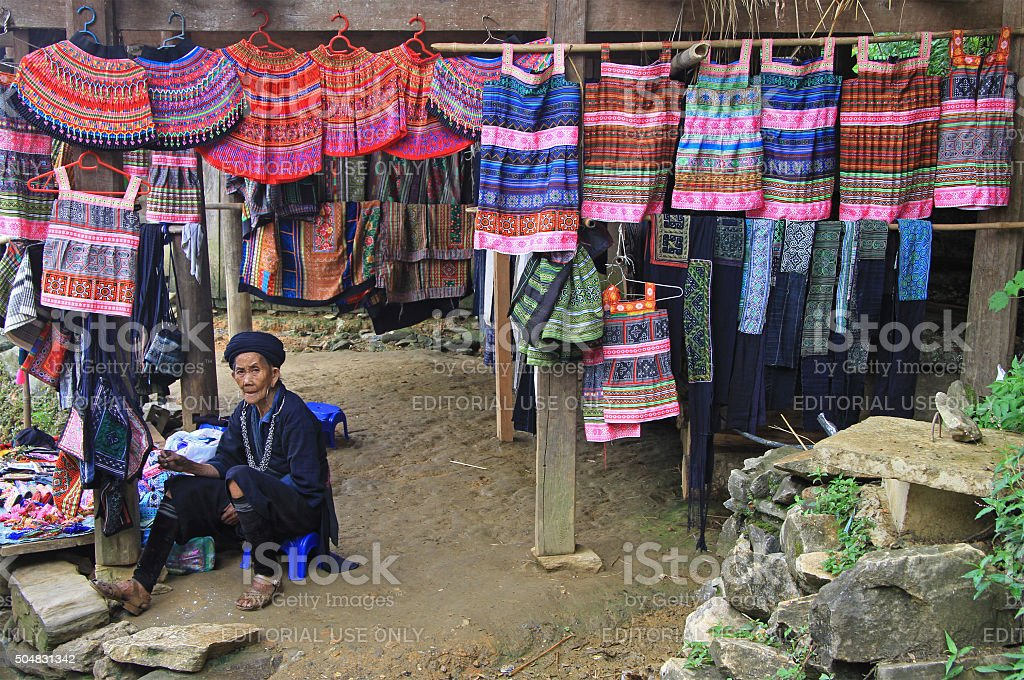 old woman is selling traditional clothes and accessories in tourist stock photo