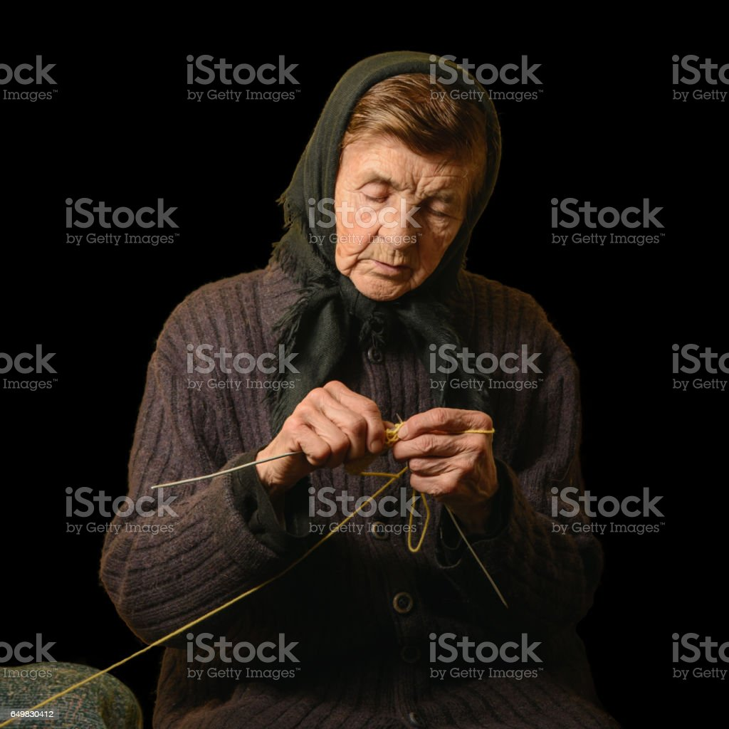 Old woman knitting. Low key photograph on black background. stock photo
