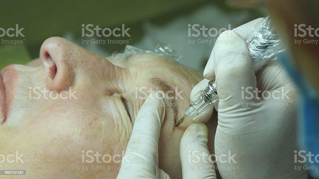 Old woman lies and getting eyelash makeup at beauty salon foto de stock libre de derechos