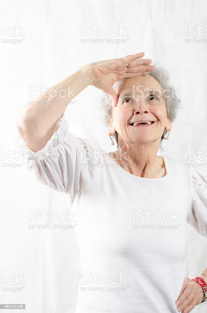 old woman looks above and smiles stock photo