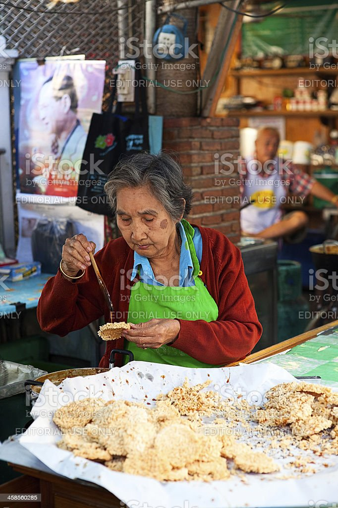 Old woman making rice cookies. Amphawa, Floating Market near Ban stock photo