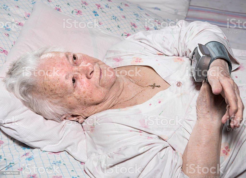 Old woman measures arterial pressure stock photo