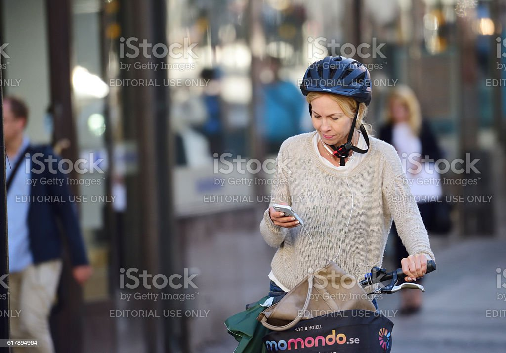 Old woman on bicycle, with headphones and mobile phone, helmet stock photo