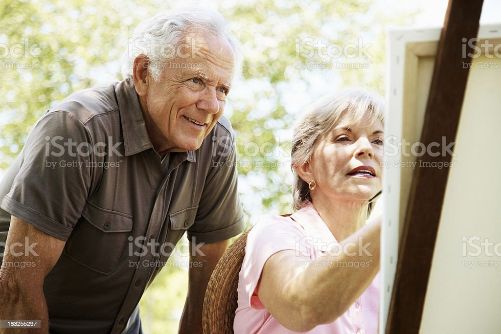 Old woman painting a picture with her husband stock photo