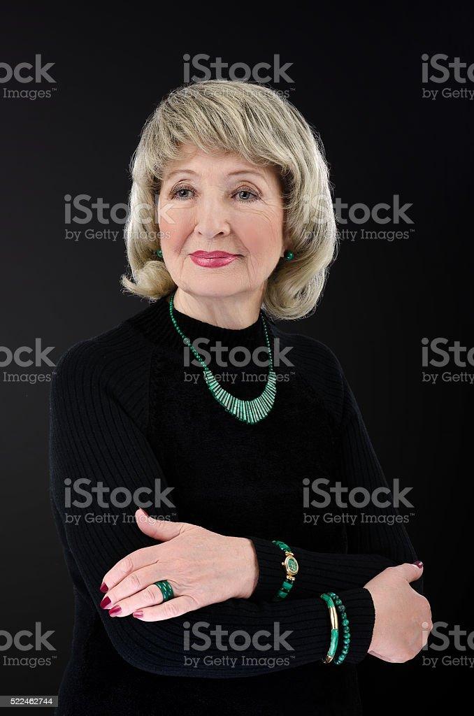 Old woman posing with malachite jewelry set stock photo