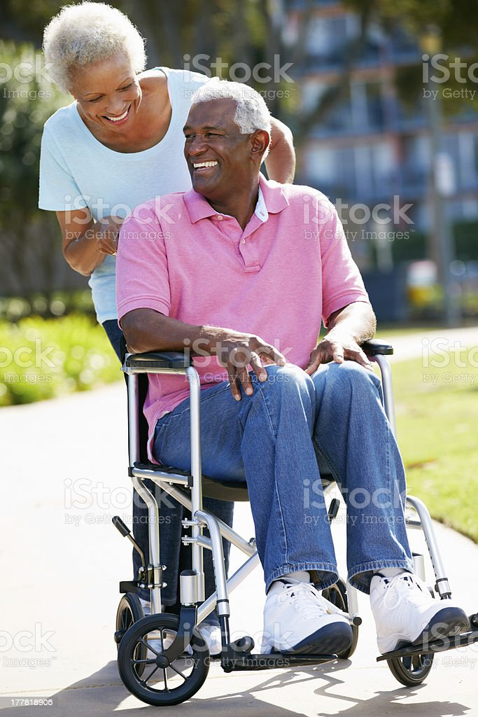 Old woman pushing her husband in wheelchair stock photo