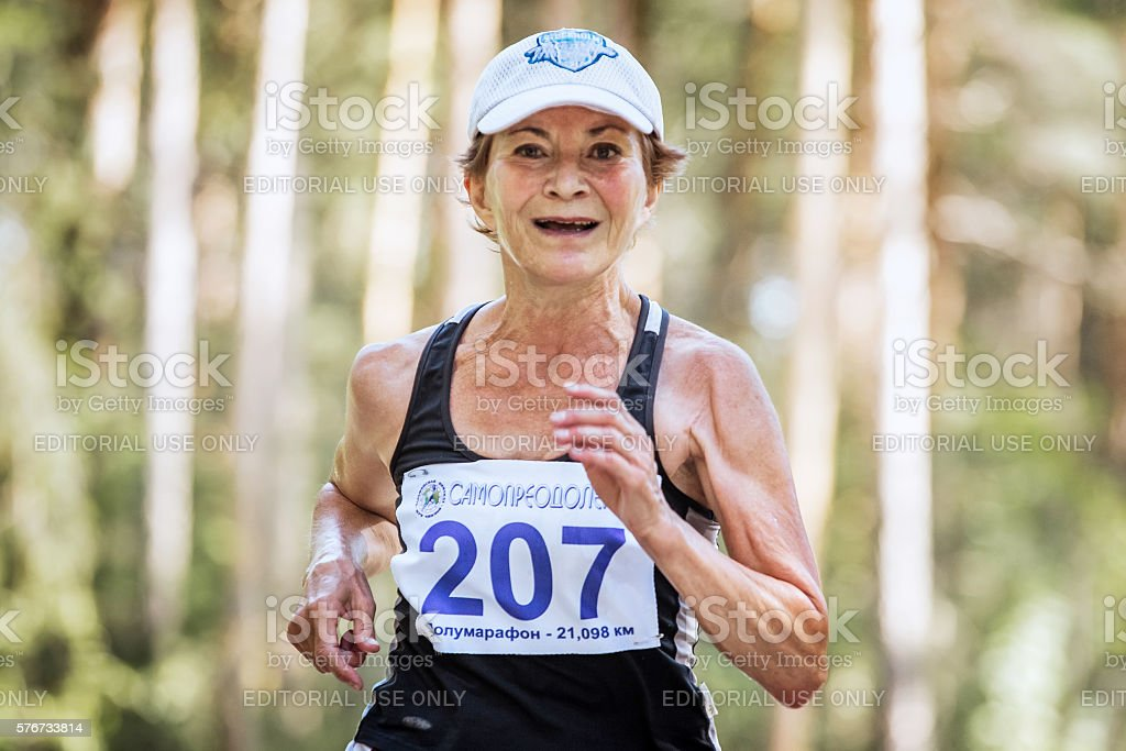 old woman runs through forest and smiling royalty-free 스톡 사진