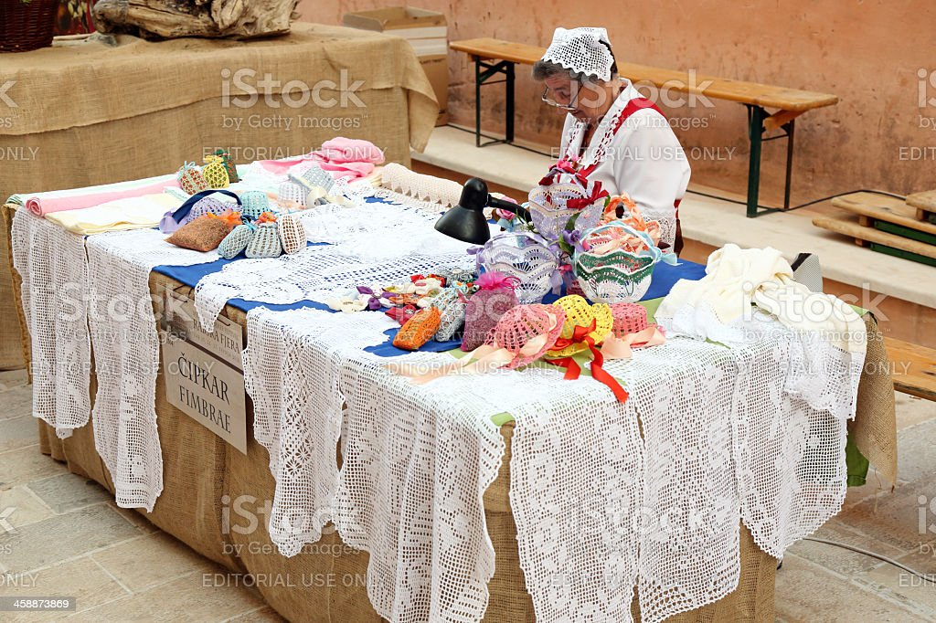 Old woman selling handmade products from Rab lace stock photo