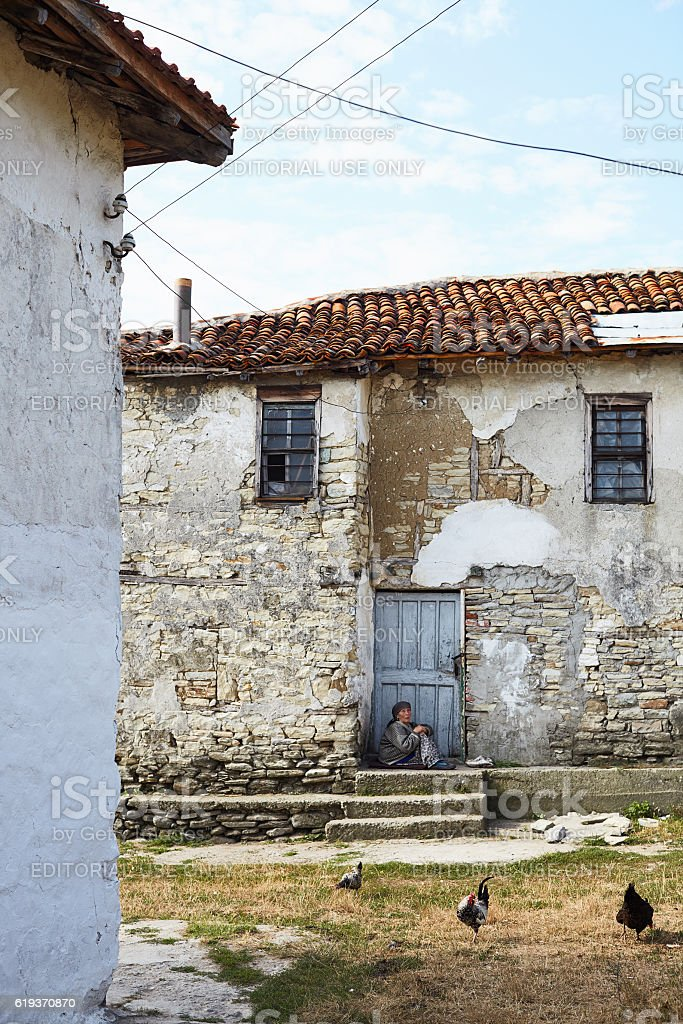 Old woman sits in front of her house. stock photo