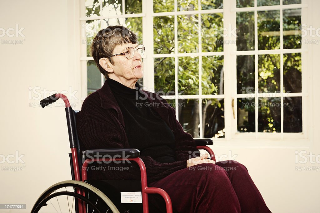 Old woman sits waiting patiently in her wheelchair royalty-free stock photo