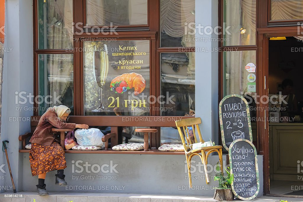 Old woman sitting near entrance of restaurant in Lviv, Ukraine stock photo