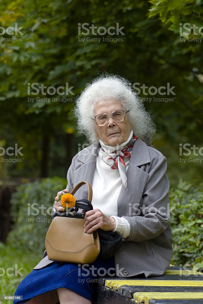 Old woman sitting on the bench royalty-free stock photo