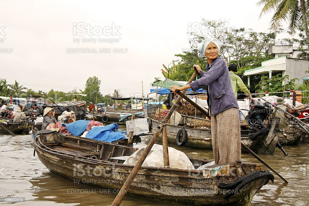 Old woman standing on her empty boat royalty-free stock photo