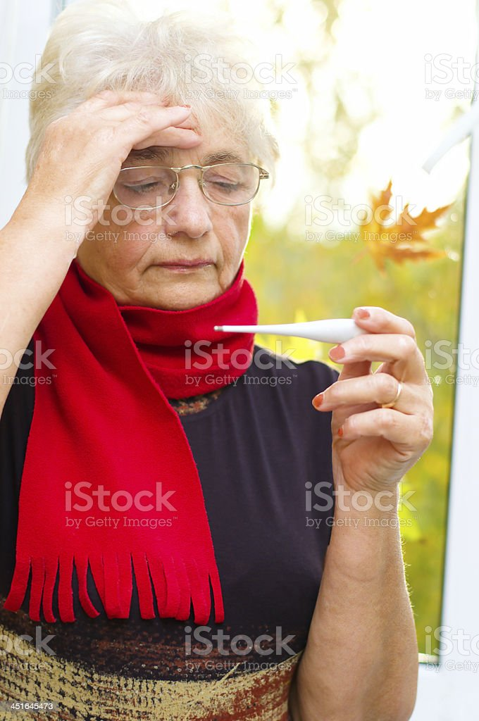 Old woman taking her temperature stock photo