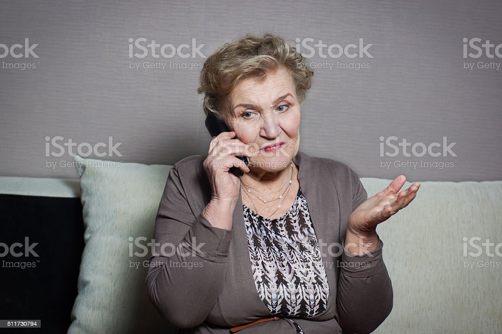 old woman talking on the phone stock photo