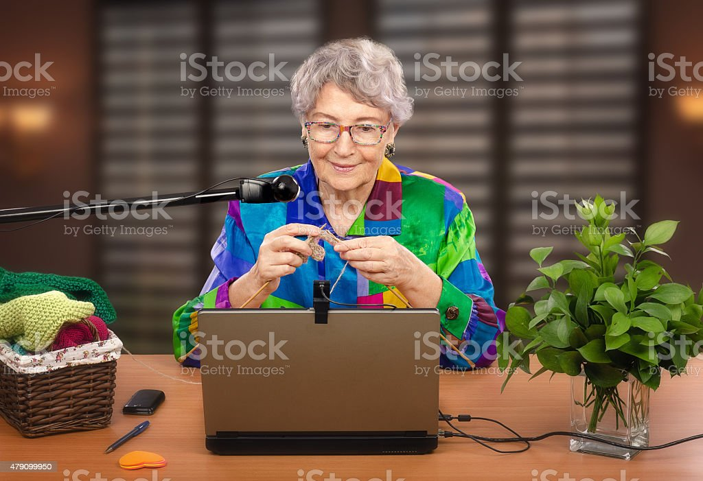 Old woman teaches knitting online stock photo