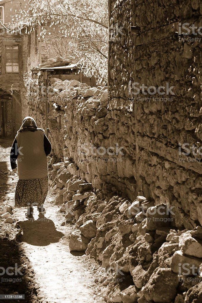 Old Woman Walking in Village stock photo