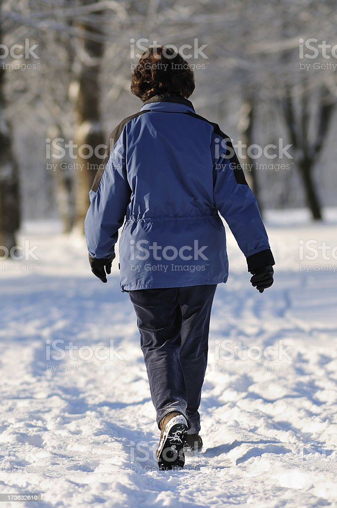 old woman walking in winter avenue royalty-free stock photo