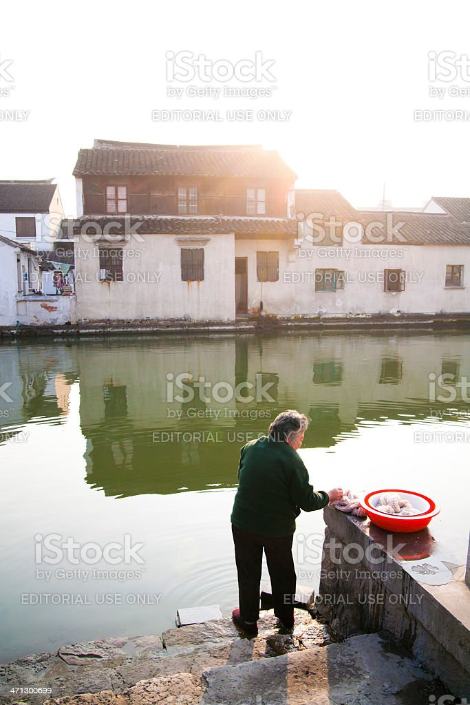 Old woman washing clothes by the river stock photo