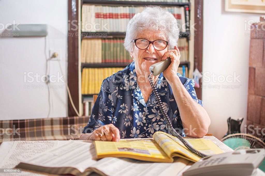 Old woman with address book talking on telephone at home. stock photo